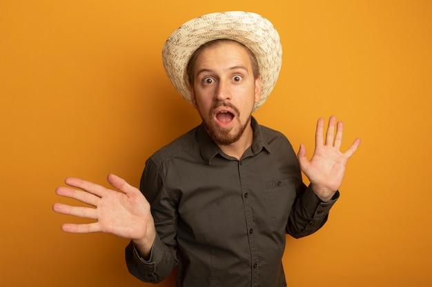 Giovane uomo bello in camicia grigia e cappello estivo sorpreso e stupito con le braccia alzate