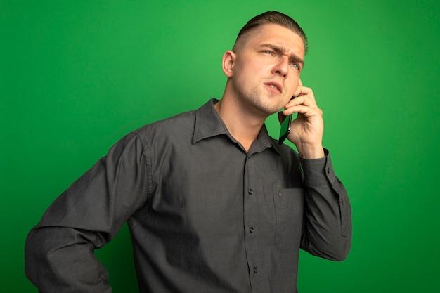 Giovane uomo bello in camicia grigia parlando al telefono cellulare con la faccia seria in piedi sopra la parete verde