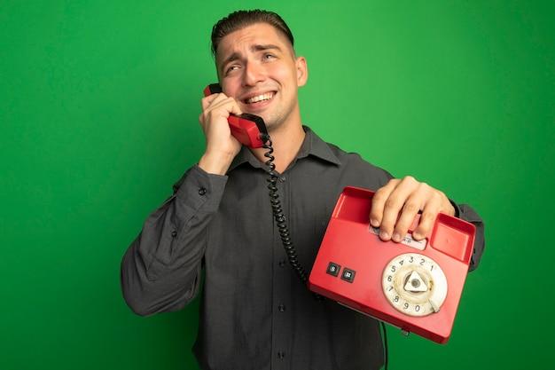 Giovane uomo bello in camicia grigia parlando al telefono vintage sorridendo allegramente in piedi sopra la parete verde