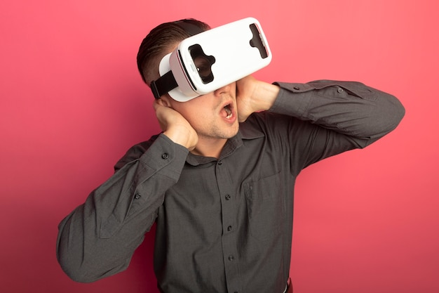 Young handsome man in grey shirt with virtual reality glasses amazed and surprised standing over pink wall