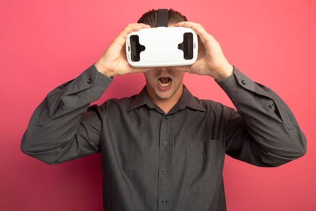 Young handsome man in grey shirt with virtual reality glasses amazed and surprised