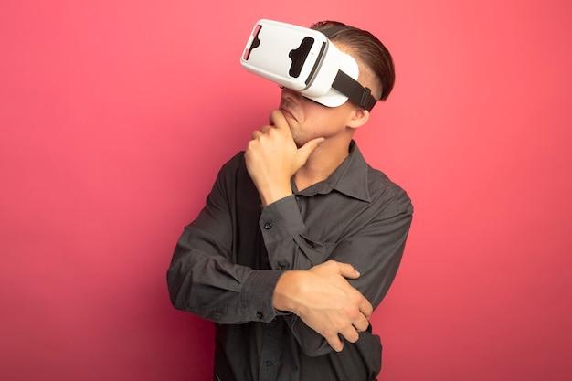 Giovane uomo bello in camicia grigia con occhiali per realtà virtuale gesticolando con le mani che guardano da parte con la mano sul mento