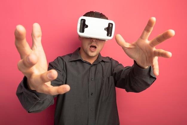 Giovane uomo bello in camicia grigia con occhiali per realtà virtuale gesticolando con le mani