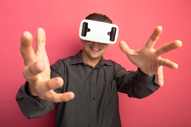 Young handsome man in grey shirt with virtual reality glasses gesturing with hands