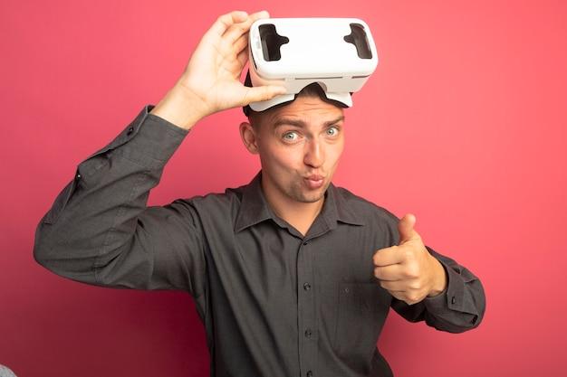 Giovane uomo bello in camicia grigia con occhiali per realtà virtuale che sembra fiducioso che mostra i pollici in su in piedi sopra il muro rosa