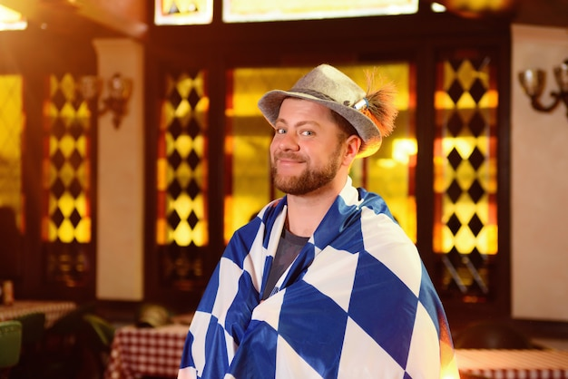 Young handsome man in hat and with beard under the flag oktoberfest showing thumb up