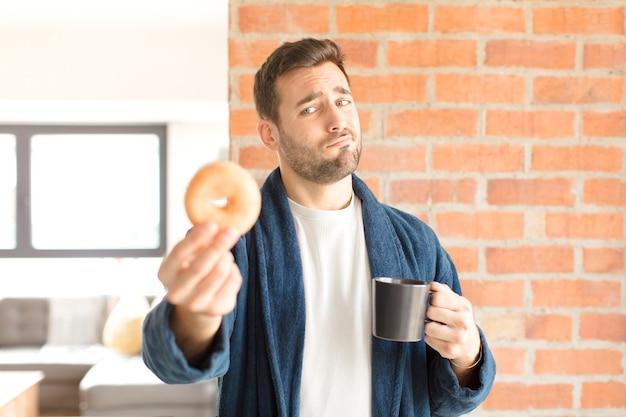 家でコーヒーを飲んでいる若いハンサムな男