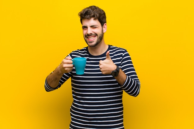 Young handsome man having a coffee against orange wall