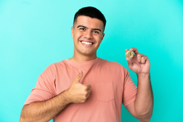 親指を立てるジェスチャーを与える孤立した青い背景の上にビットコインを保持している若いハンサムな男