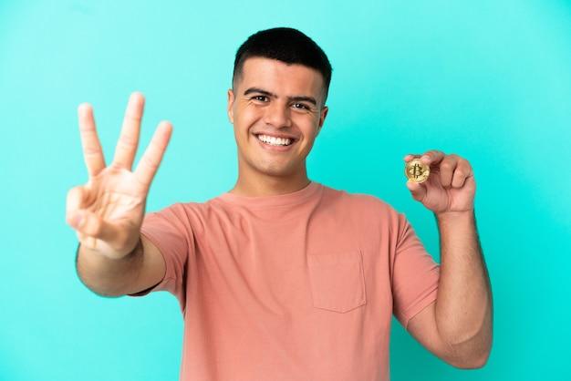 Молодой красавец, держащий биткойн на синем фоне, счастлив и считает три пальцами