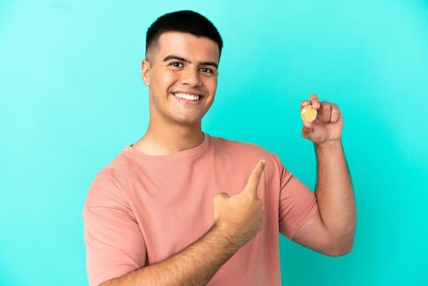 Молодой красивый мужчина держит биткойн на изолированном синем фоне, указывая назад