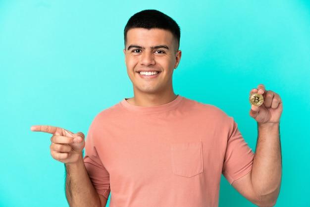Молодой красивый мужчина держит биткойн на синем фоне, указывая пальцем в сторону