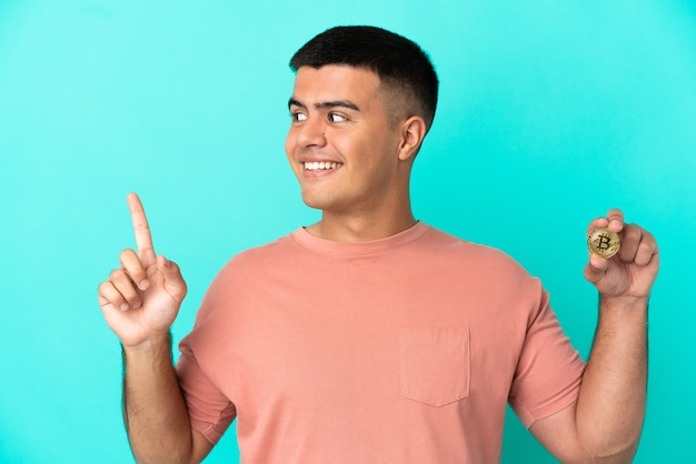 Молодой красивый мужчина держит биткойн на синем фоне, указывая на отличную идею