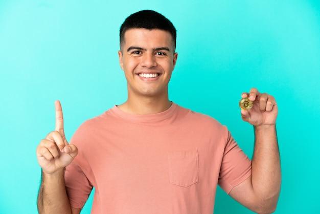 Молодой красавец, держащий биткойн на синем фоне, показывает и поднимает палец в знак лучших