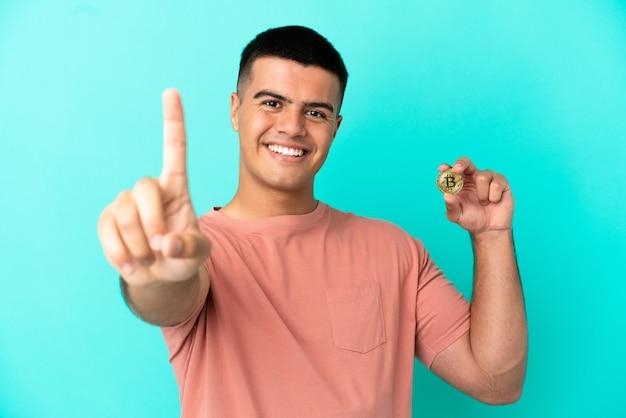 Молодой красавец, держащий биткойн на изолированном синем фоне, показывает и поднимает палец
