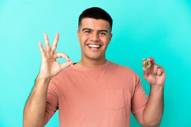 Молодой красивый мужчина держит биткойн на синем фоне, показывая пальцами знак ок