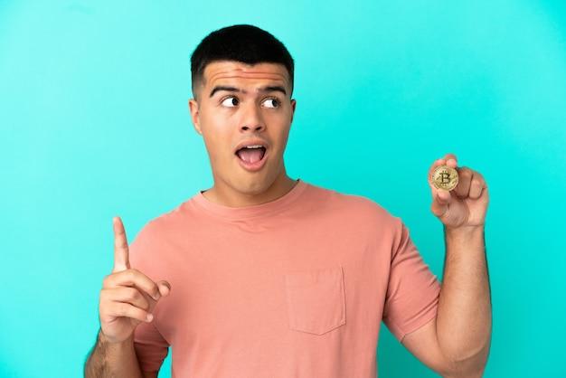 指を上に向けるアイデアを考えて孤立した青い背景の上にビットコインを保持している若いハンサムな男