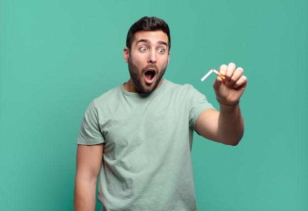 タバコを持っている若いハンサムな男。禁煙の概念