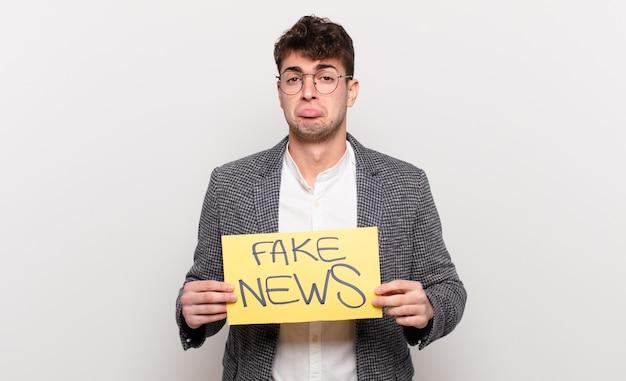 偽のニュース看板を持っている若いハンサムな男