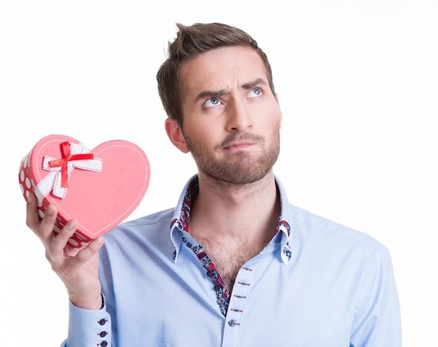 Молодой красивый мужчина держит подарок и думает - изолированные на белом.