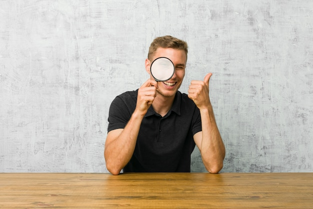 Молодой красивый мужчина держит увеличительное стекло, улыбаясь и поднимая палец вверх