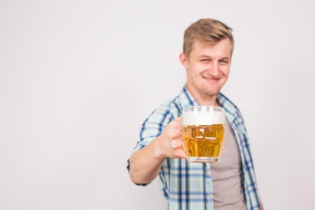 맥주 머그잔을 들고 젊은 잘 생긴 남자. 복사 공간 배경입니다.