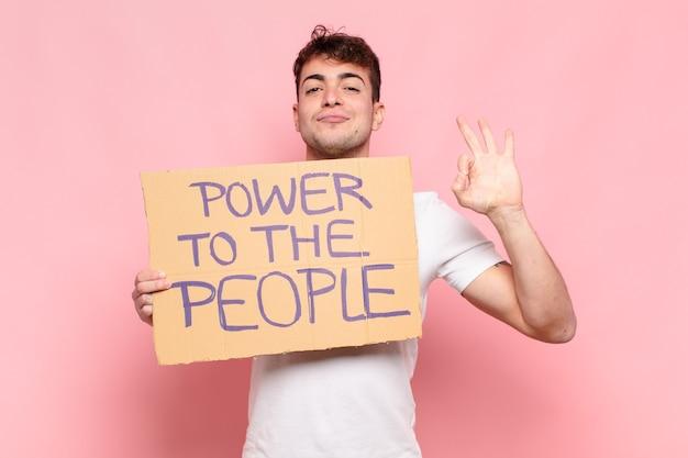 テキストのプラカードを持っている若いハンサムな男:人々への力