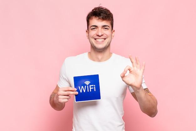 Wi-fiの看板を持っている若いハンサムな男