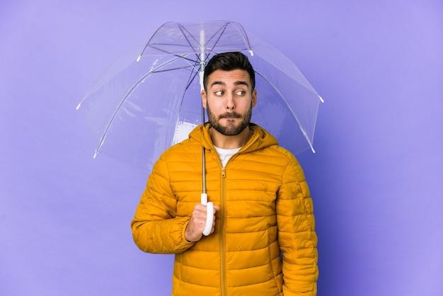 Молодой красивый мужчина, держащий изолированный зонтик, смущен, чувствует себя сомнительным и неуверенным.