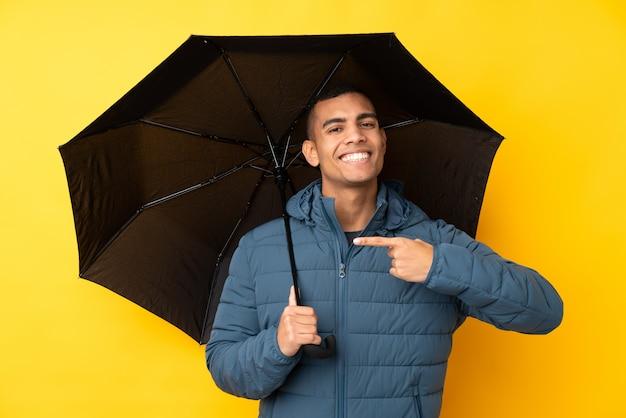 Молодой красивый мужчина держит зонтик над желтой стене и указывая его