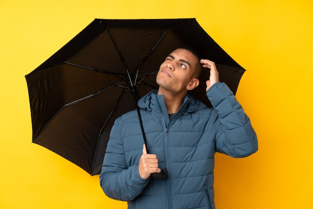 Молодой красивый человек, держащий зонтик над изолированной желтой стеной, с сомнениями и с путанным выражением лица