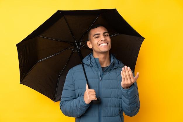 Молодой красивый человек, держащий зонтик над изолированной желтой стеной, приглашая прийти с рукой. рад, что ты пришел
