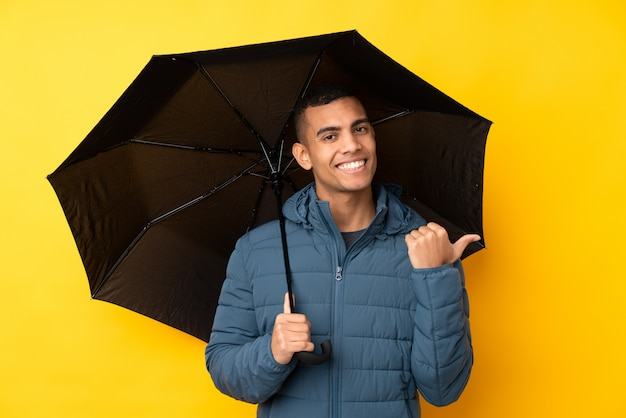 Молодой красивый мужчина держит зонтик над желтой стене, указывая в сторону, чтобы представить продукт