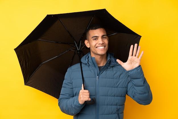 Молодой красивый мужчина держит зонтик над желтой стеной, салютов с рукой с счастливым выражением
