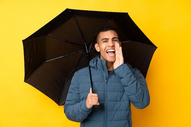 Молодой красивый мужчина держит зонтик над желтой стене, крича с широко открытым ртом