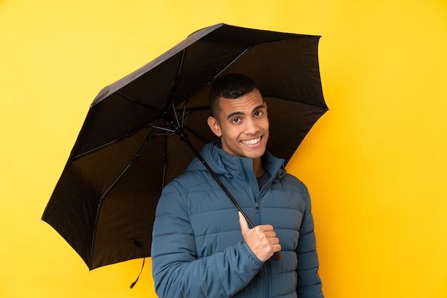 Молодой красивый мужчина держит зонтик над желтой стене с счастливым выражением