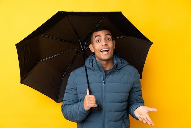 Молодой красивый мужчина держит зонтик над желтой стене с шокирован выражением лица
