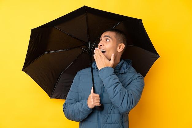 Молодой красивый мужчина держит зонтик над желтой стене с удивлением и шокирован выражением лица