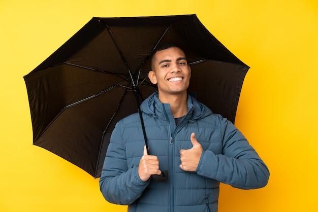 Молодой красивый мужчина держит зонтик над желтой стене с большими пальцами руки вверх, потому что случилось что-то хорошее