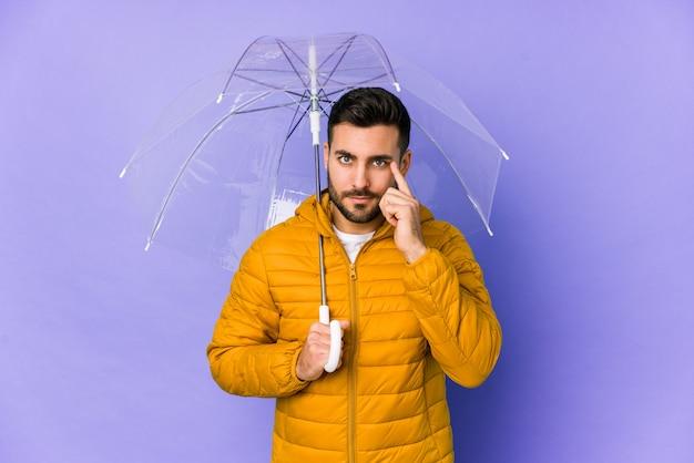 Молодой красивый мужчина держит зонтик, указывая храм с пальцем, думая, сосредоточены на задаче.