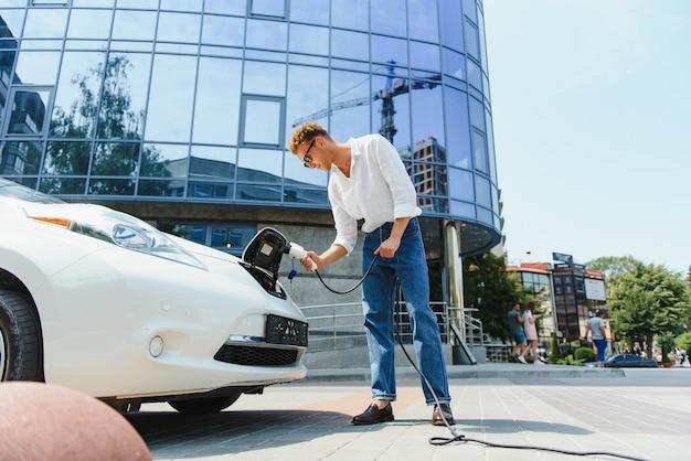 Молодой красавец, держащий зарядный кабель на электрической зарядной станции, стоит возле своей новой машины, выглядит довольным.