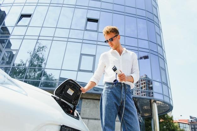 그의 새 차 근처에 서 있는 전기 충전소 지점에서 충전 케이블을 들고 있는 젊고 잘생긴 남자는 만족스러워 보입니다.
