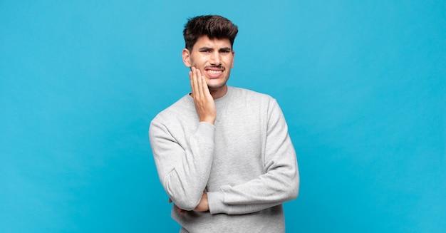 Молодой красивый мужчина держится за щеку и страдает от болезненной зубной боли, чувствует себя больным, несчастным и несчастным, ищет стоматолога