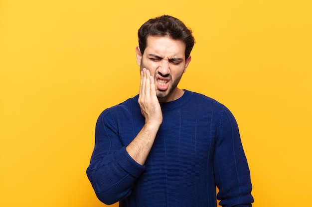 Young handsome man holding cheek and suffering painful toothache, feeling ill, miserable and unhappy, looking for a dentist