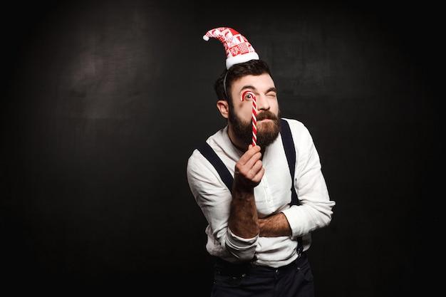 Молодой красивый человек держа конфету рождества над чернотой.