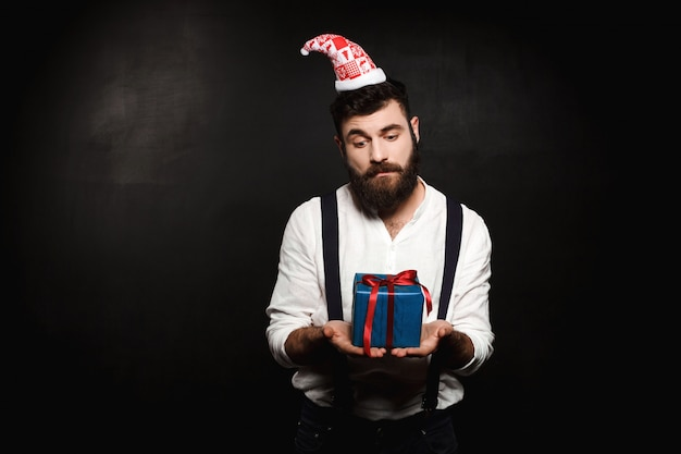 Young handsome man holding christmas gift box over black.
