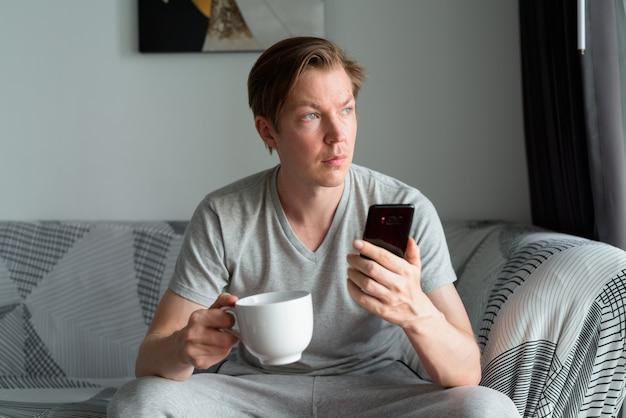 家で考えながらコーヒーカップと電話を保持している若いハンサムな男
