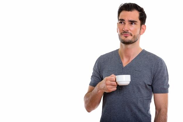考えながらコーヒーカップを保持している若いハンサムな男