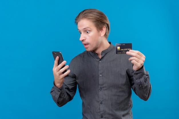 クレジットカードを保持していると彼のスマートフォンの画面を見て、青い壁の上に立っている若いハンサムな男