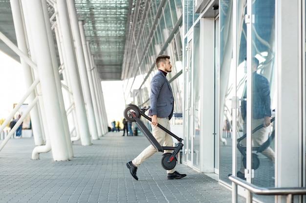 Молодой красавец холдинг e скутер приходит в аэропорту. аренда транспорта в поездке